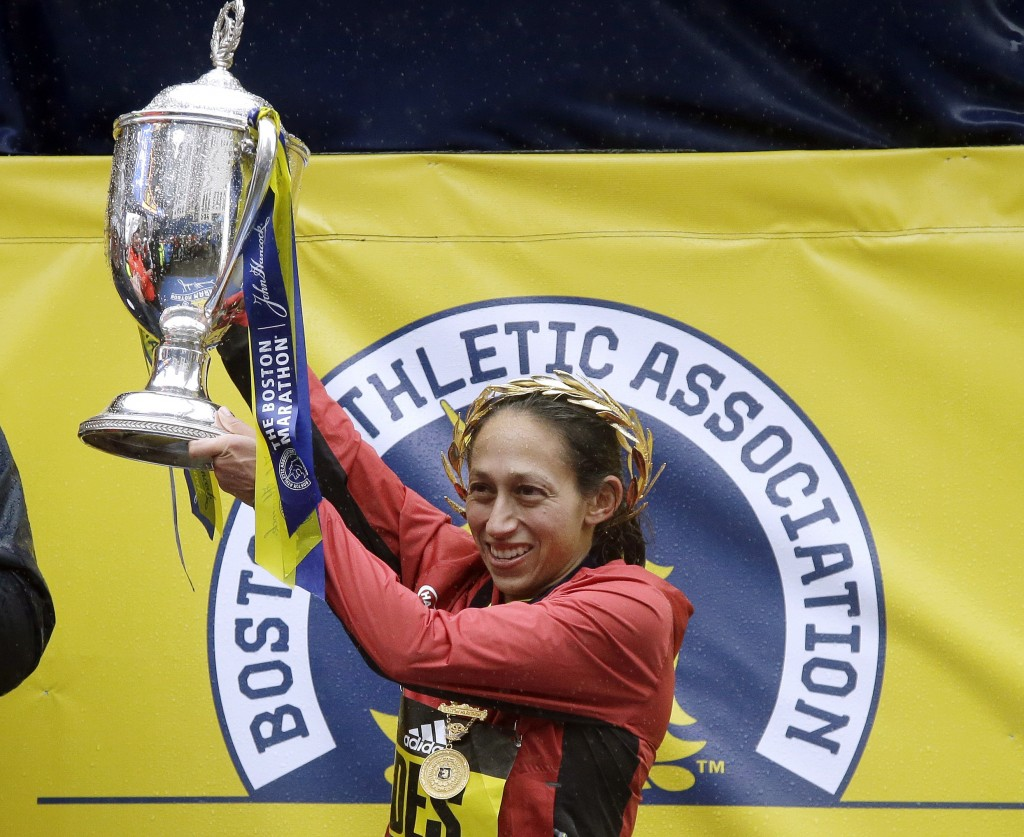 FILE- In this April 16, 2018, file photo, Desiree Linden, of Washington, Mich., hoists the trophy after winning the women's division of the 122nd Bost...