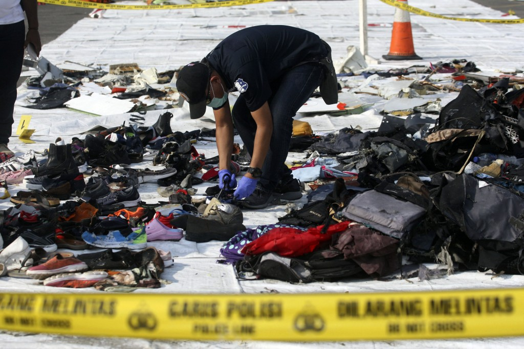 An investigator inspect debris from Lion Air flight JT 610 that crashed into the Java sea on Monday, at Tanjung Priok Port in Jakarta, Indonesia, Frid