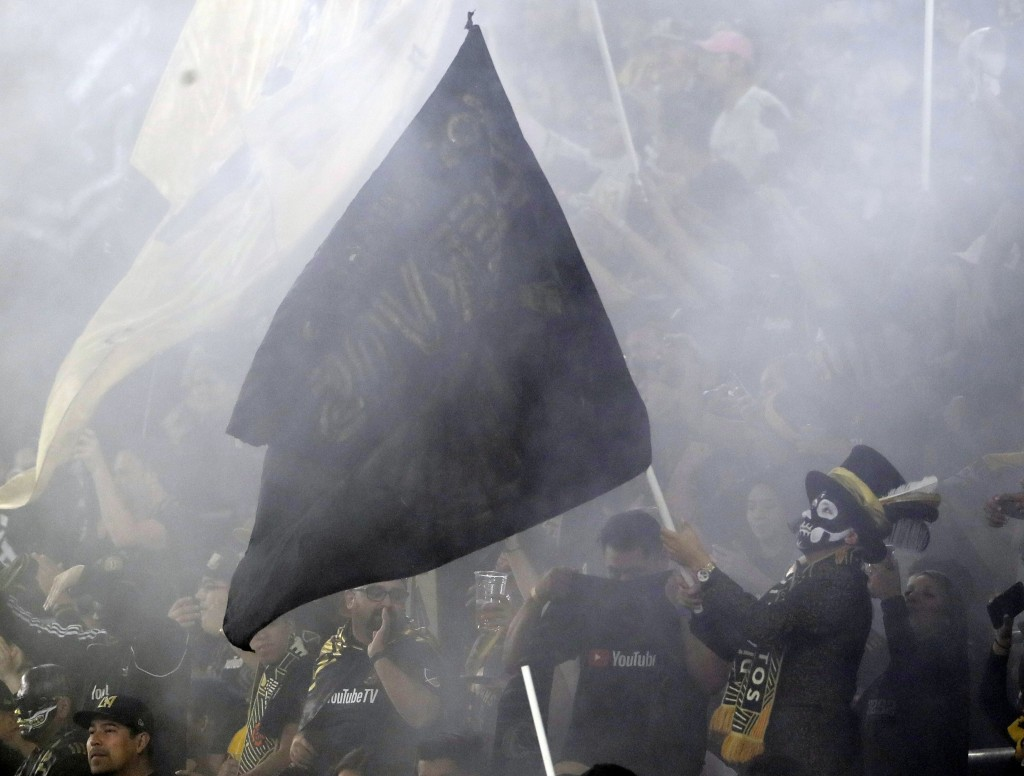 A Los Angeles FC Fan waves a flag during the first half of the team's MLS soccer playoff match against Real Salt Lake on Thursday, Nov. 1, 2018, in Lo...