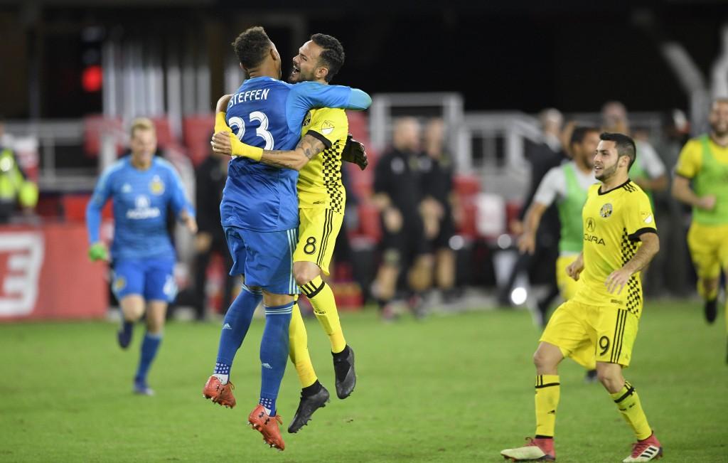 Columbus Crew SC goalkeeper Zack Steffen (23) celebrates with midfielder Artur (8) and defender Milton Valenzuela, right, after winning an MLS playoff
