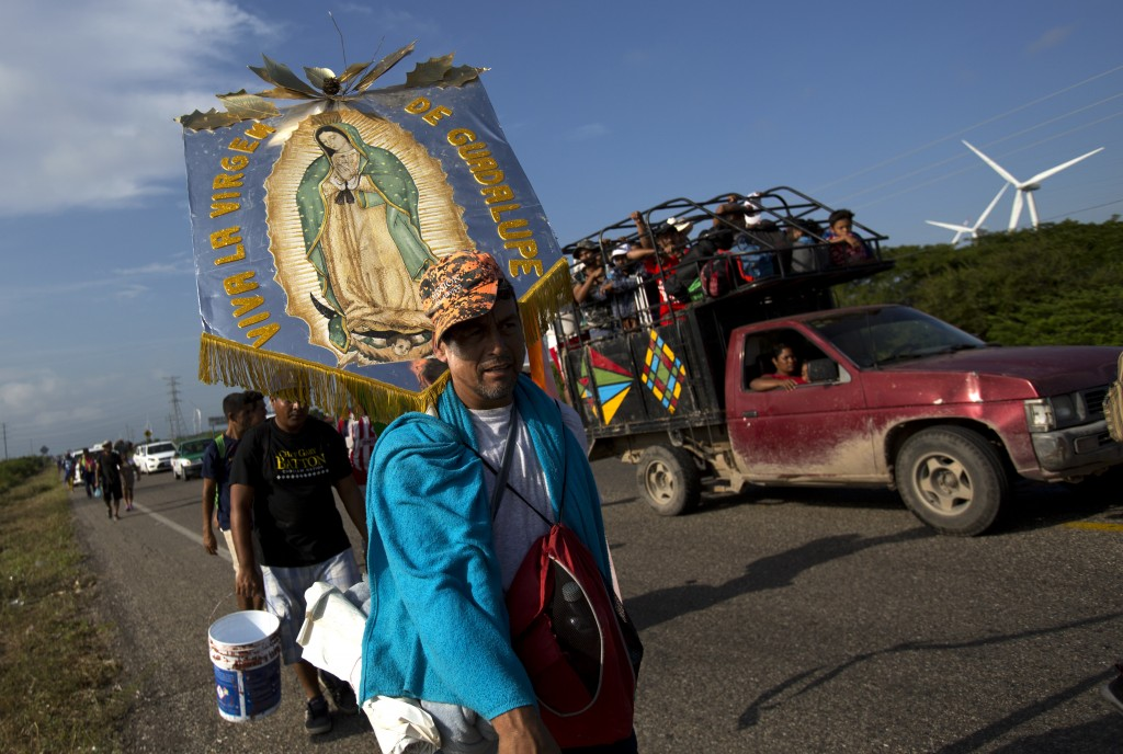 Erlin Troches, a 43-year-old Honduran migrant from the city of Santa Barbara, carries an image of the Virgin of Guadalupe that was given to him by a p...