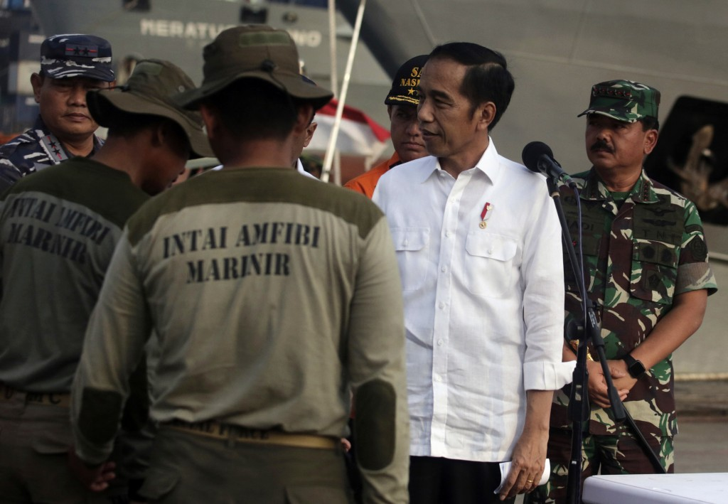 Indonesian President Joko Widodo, second right, congratulates navy divers who found the flight data recorder from the crashed Lion Air jet as Armed Fo...