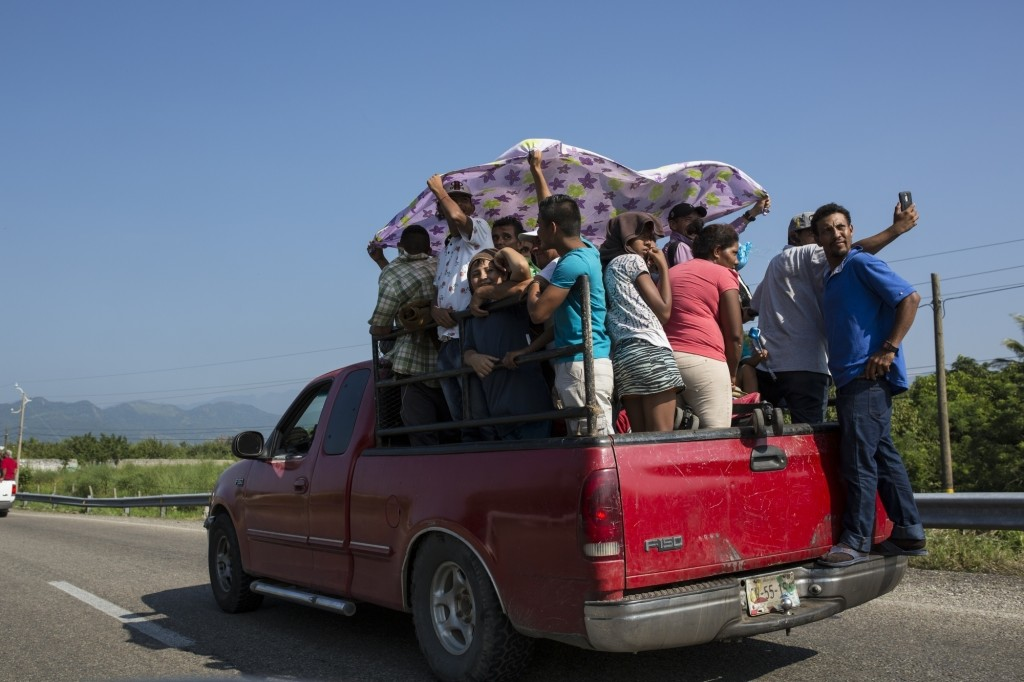 Joel Eduardo Espinar stands on the bumper of a pick-up truck as his family and others arrive in Arriaga, Mexico. Four of Espinar's friends in Honduras...