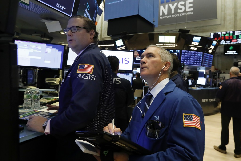 FILE- In this Oct. 24, 2018, file photo specialist Gregg Maloney, left, and trader Timothy Nick work on the floor of the New York Stock Exchange. The ...