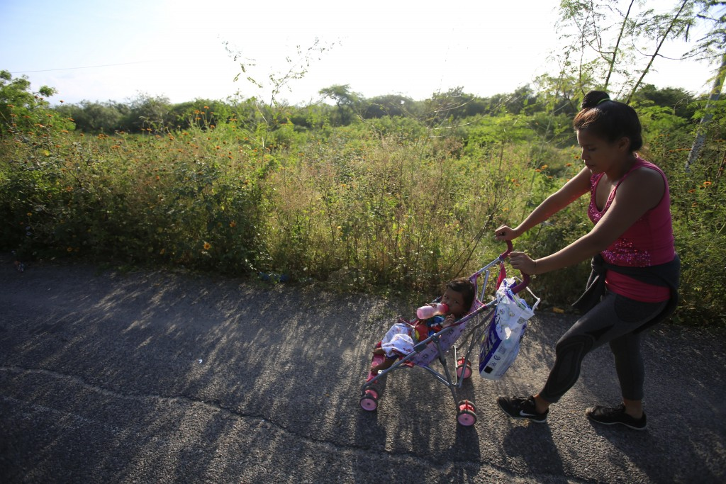A woman pushes her daughter in a stroller as a thousands-strong caravan of Central Americans hoping to reach the U.S. border moves onward from Juchita...