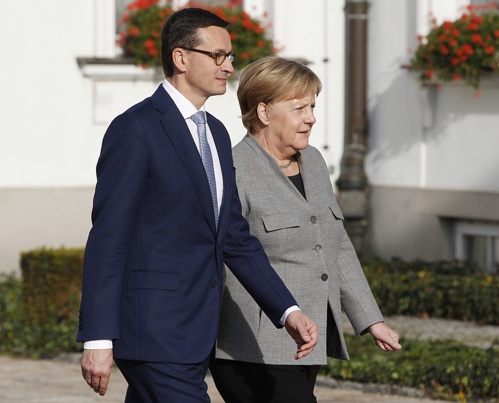 Polish Prime Minister Mateusz Morawiecki, left, welcomes German Chancellor Angela Merkel, right, ahead of intergovernmental consultations in Warsaw, P