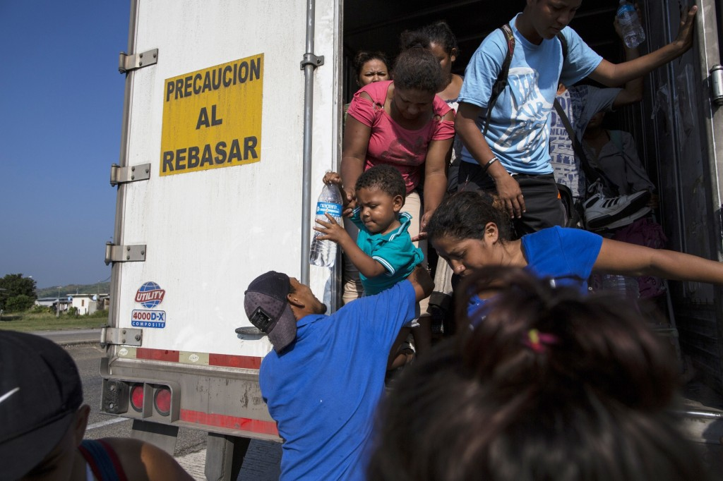 Joel Eduardo Espinar reaches for his son, Eduardo, 2, from his wife, Yamilet, while arriving in Arriaga, Mexico, after a ride on a truck. His plan is ...