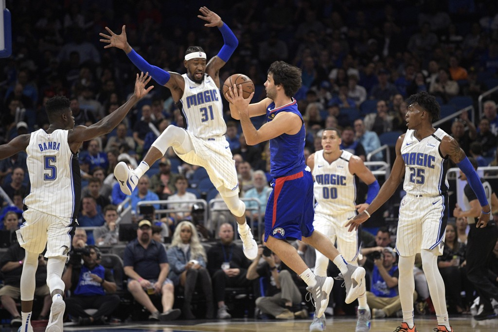 Los Angeles Clippers guard Milos Teodosic, center, passes the ball in front of Orlando Magic center Mohamed Bamba (5), guard Terrence Ross (31), forwa