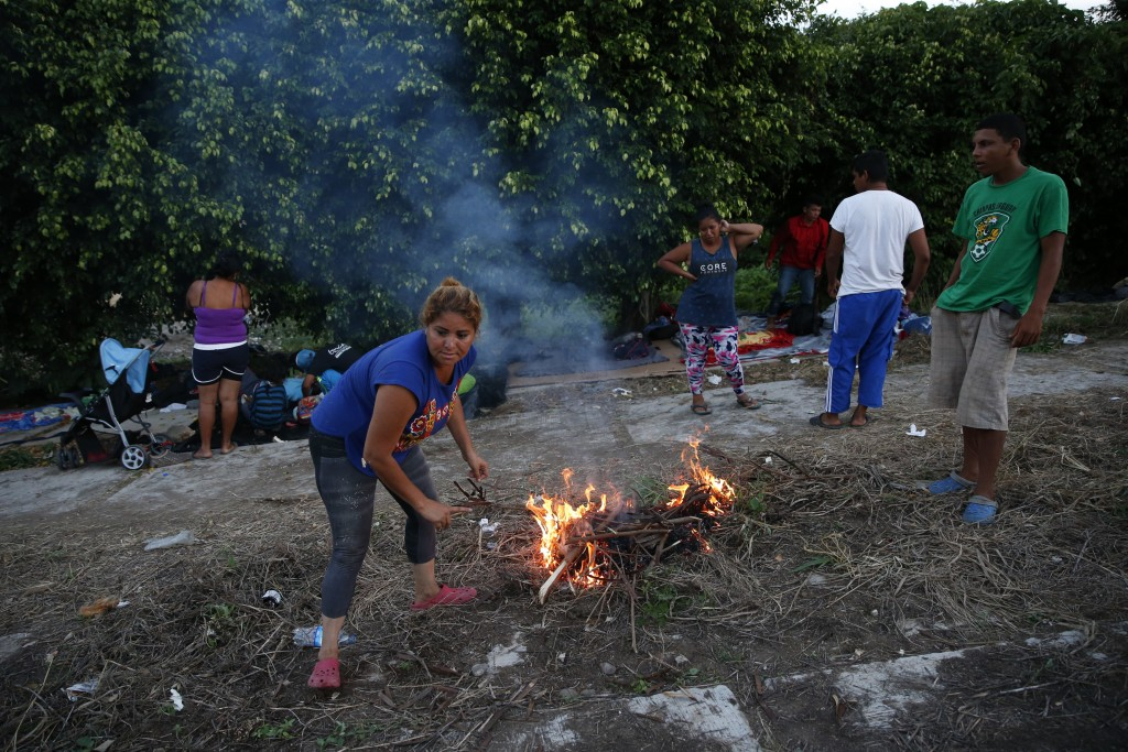 Migrants light a fire for cooking as a thousands-strong caravan of Central Americans hoping to reach the U.S. border stops for the night, in Matias Ro...