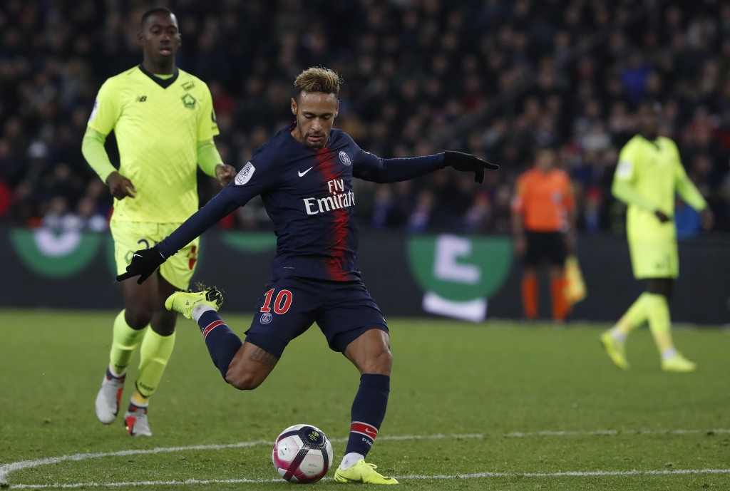 PSG's Neymar, center, shots to score his side second goal during the League One soccer match between Paris Saint-Germain and Lille at the Parc des Pri...