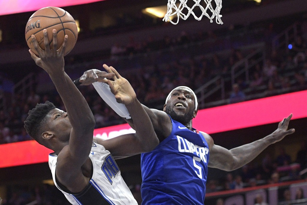 Orlando Magic center Mohamed Bamba, left, is fouled by Los Angeles Clippers forward Montrezl Harrell (5) while going up for a shot during the first ha...
