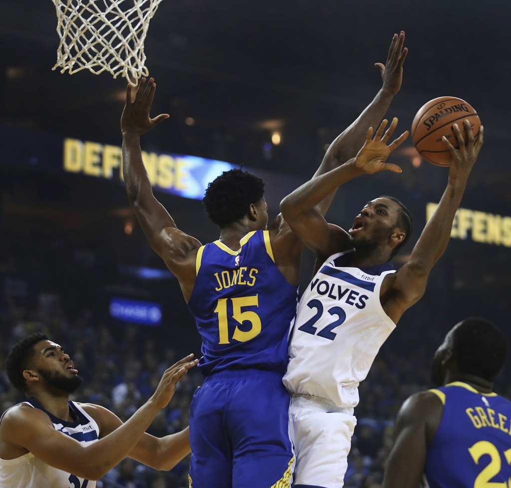 Minnesota Timberwolves' Andrew Wiggins, right, shoots over Golden State Warriors' Damian Jones (15) during the first half of an NBA basketball game Fr...