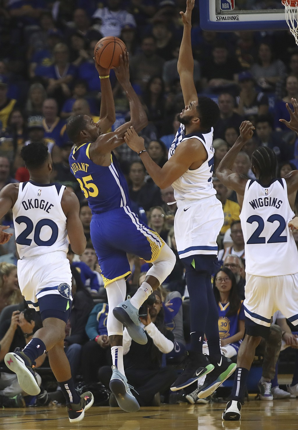 Golden State Warriors' Kevin Durant (35) shoots as Minnesota Timberwolves' Karl-Anthony Towns (32) defends during the first half of an NBA basketball