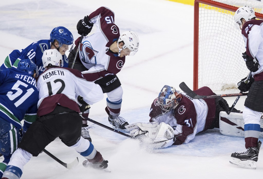 Vancouver Canucks' Elias Pettersson (40), of Sweden, scores against Colorado Avalanche goalie Philipp Grubauer (31), of Germany, as Avalanche's Sheldo