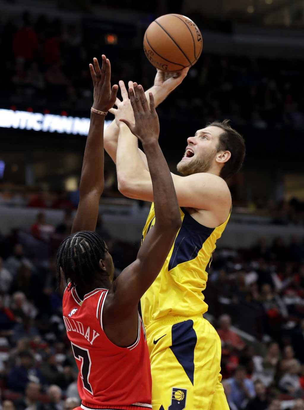 Indiana Pacers forward Bojan Bogdanovic, right, shoots against Chicago Bulls guard Justin Holiday during the first half of an NBA basketball game Frid...