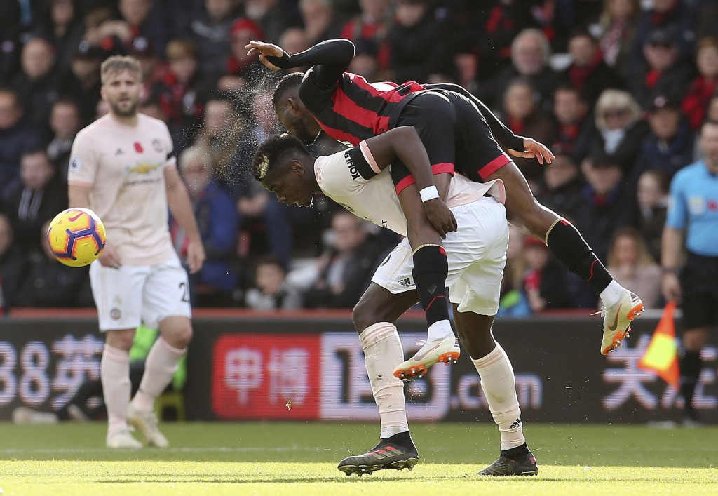 Bournemouth's Jefferson Lerma, bottom, and Manchester United's Paul Pogba battle for the ball during the English Premier League soccer match between B...
