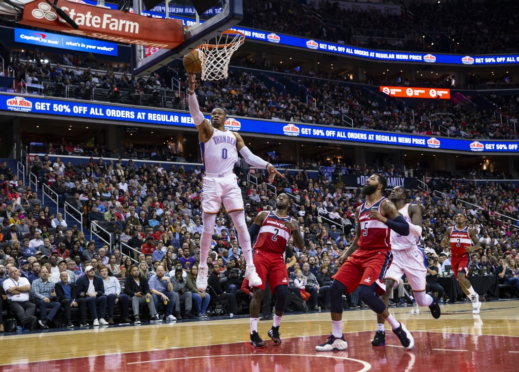 Oklahoma City Thunder guard Russell Westbrook (0) goes for a layup past Washington Wizards guard John Wall (2) and forward Markieff Morris (5) during ...