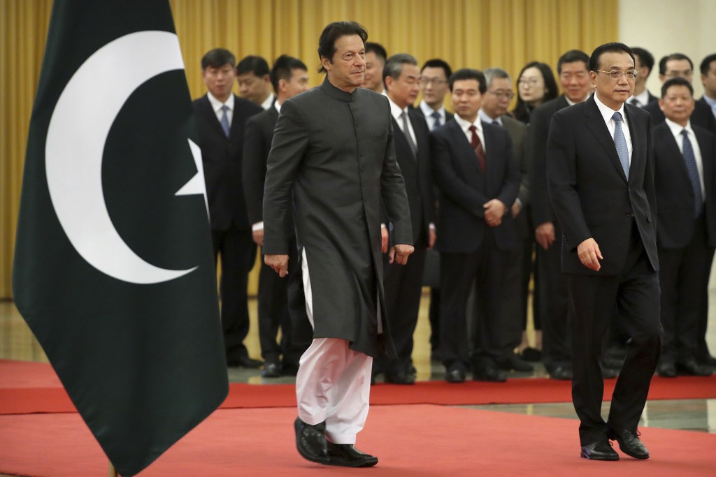 Pakistan's Prime Minister Imran Khan, left, and Chinese Premier Li Keqiang walk together during a welcome ceremony at the Great Hall of the People in