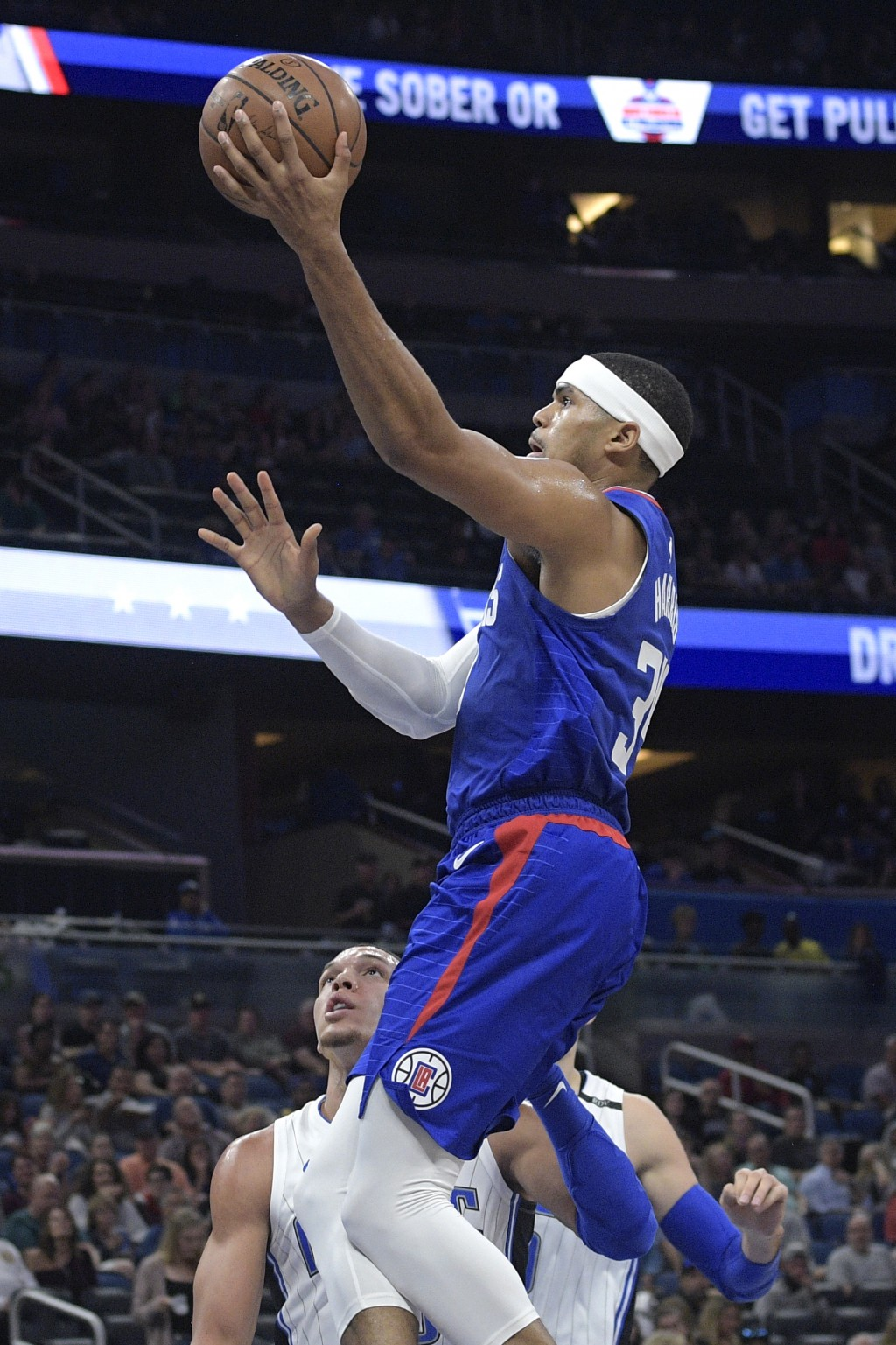 Los Angeles Clippers forward Tobias Harris goes up for a shot in front of Orlando Magic forward Aaron Gordon during the first half of an NBA basketbal