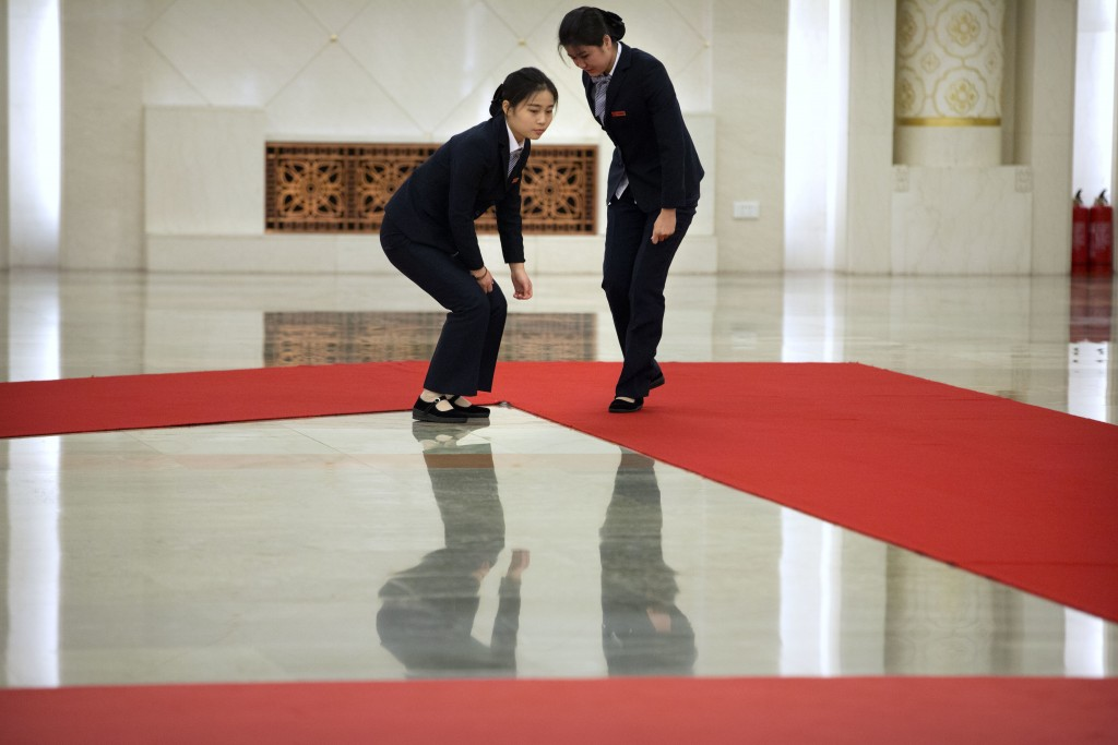 Staff members adjust a red carpet before a welcome ceremony for Pakistan's Prime Minister Imran Khan at the Great Hall of the People in Beijing, Satur...