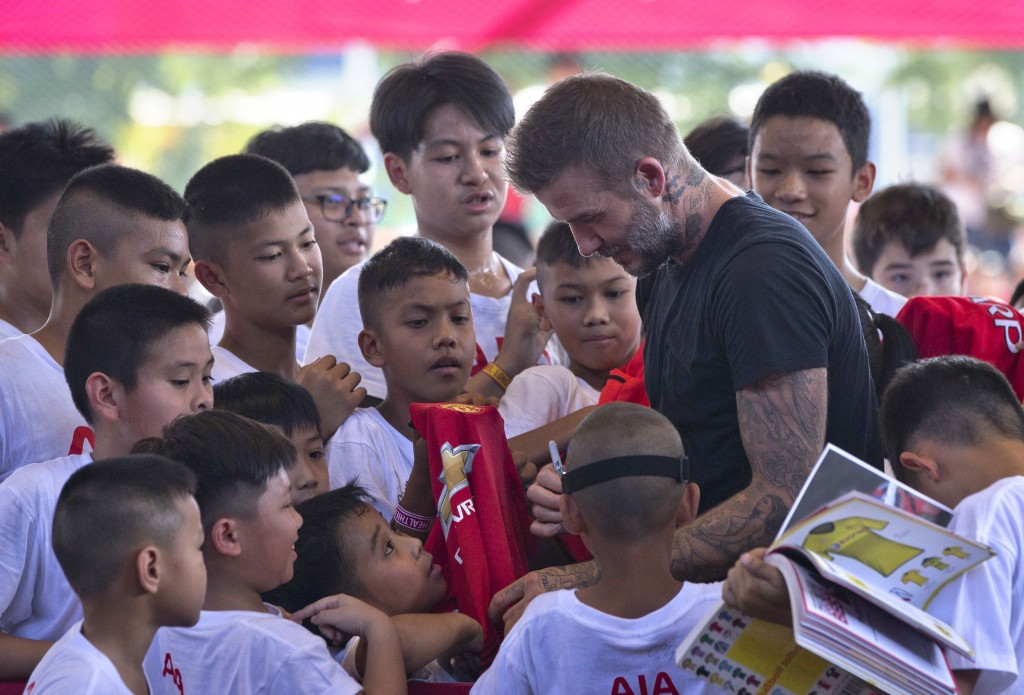 Young soccer fans gather around David Beckham to get his signature on their memorabilia during a sponsored promotional event in Bangkok, Thailand, Sat