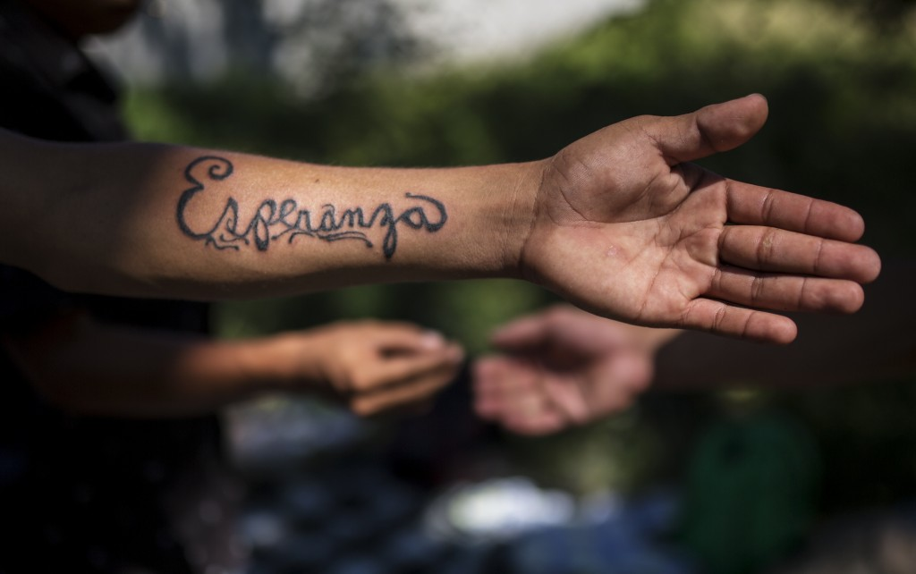 In this Oct. 31, 2018 photo, Honduran migrant Gerson Noel Rivas shows the tattoo made by fellow migrant Jose Manuel de Jesus Sandoval, at a camp set u...