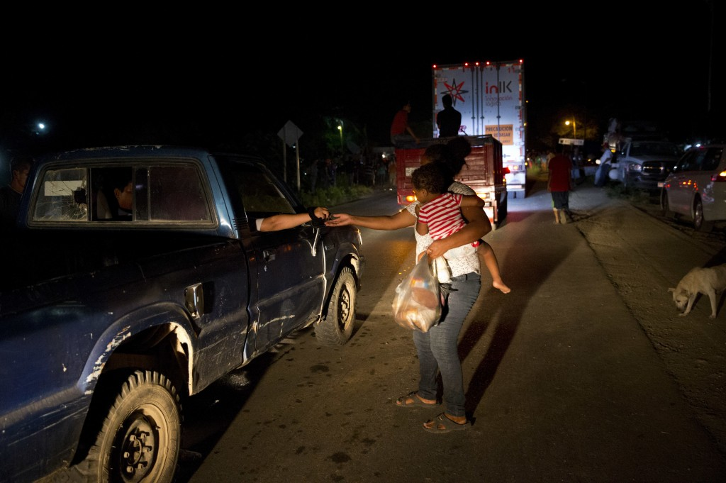 Honduran migrant Luz  Padilla Valverde, carrying her child, gets a contribution from a passing driver in Matias Romero, Oaxaca state, Mexico, Thursday...