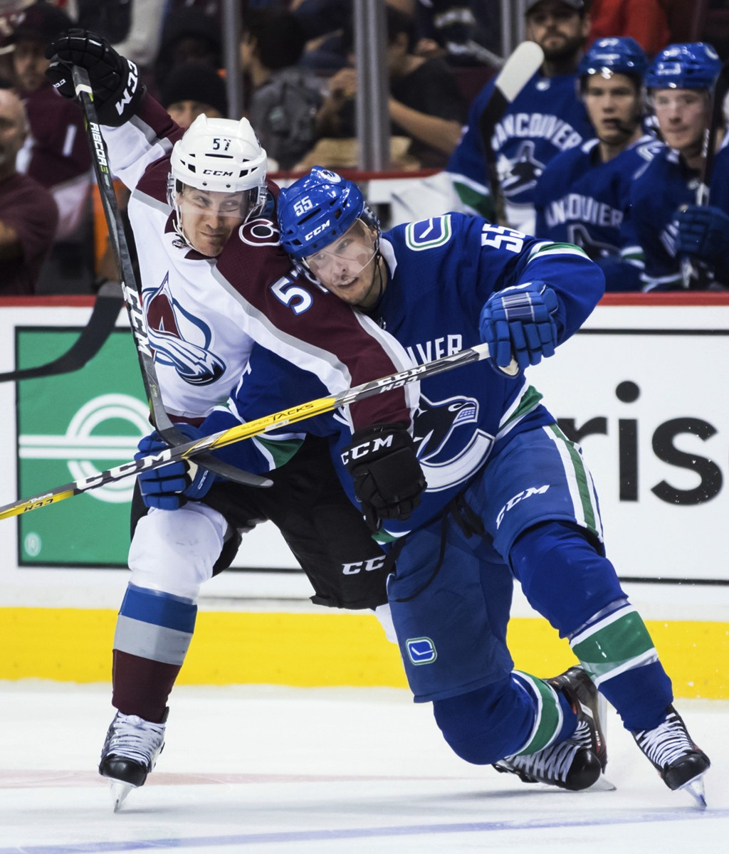 Colorado Avalanche left wing Gabriel Bourque (57) and Vancouver Canucks' Alex Biega tie each other up during the third period of an NHL hockey game Fr