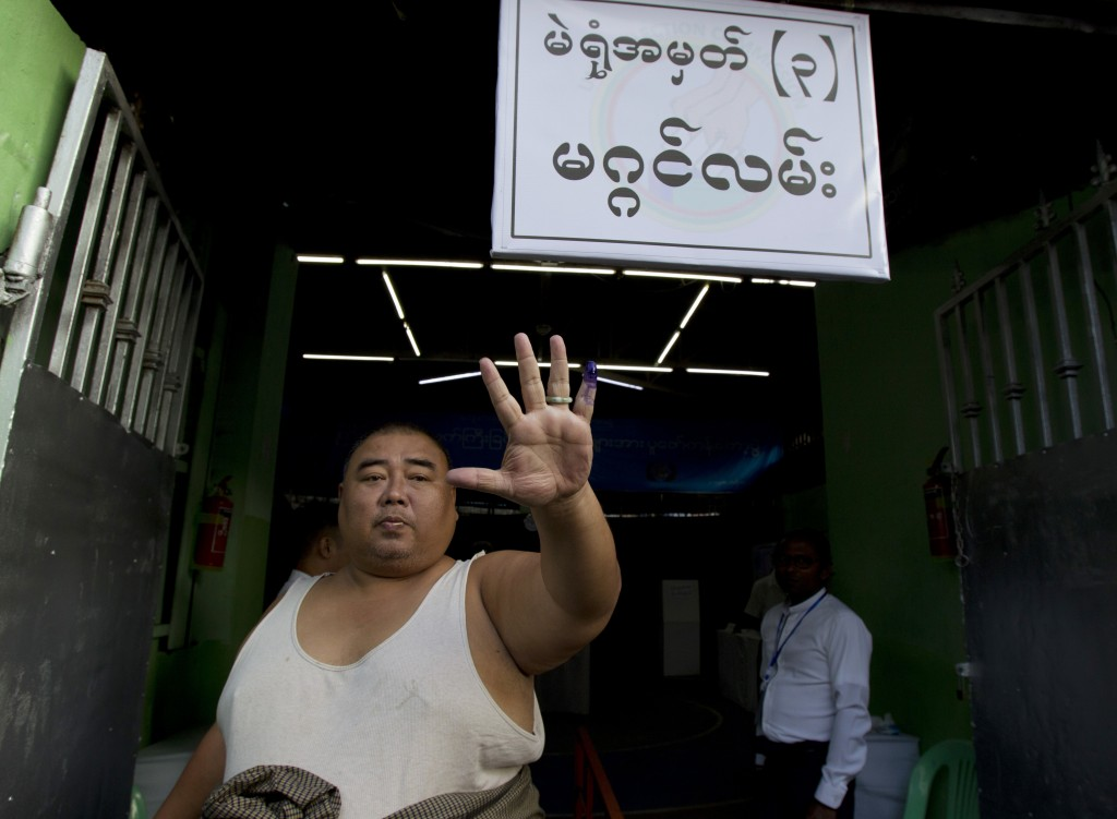 A man shows off his finger marked with ink indicating he voted as he leaves a polling station in Yangon, Myanmar, Saturday, Nov. 3, 2018. Myanmar stag