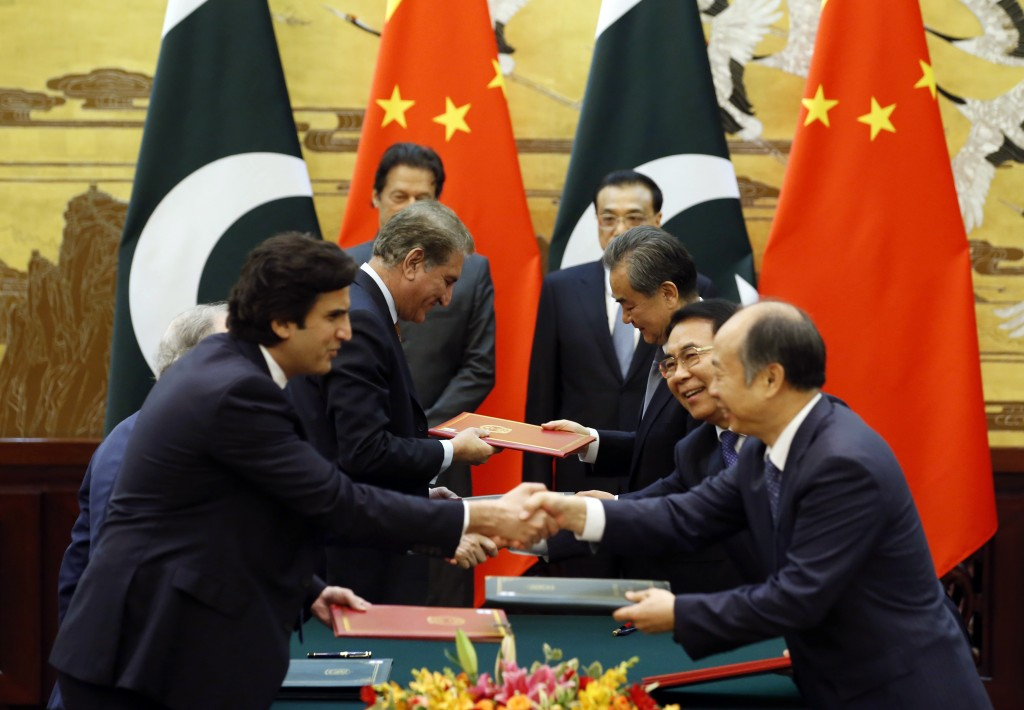 Officials change documents as Pakistani Prime Minister Imran Khan, rear left, and China's Premier Li Keqiang, rear right, attend a signing ceremony at