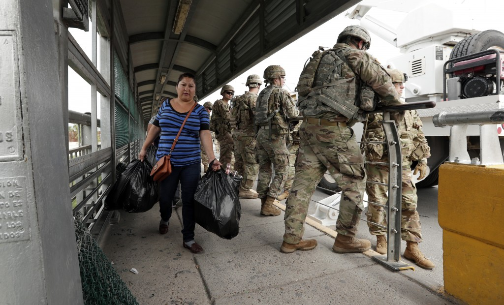 Pedestrians pass members of the U.S. military working to place razor wire along the U.S.-Mexico border on the McAllen-Hidalgo International Bridge, Fr