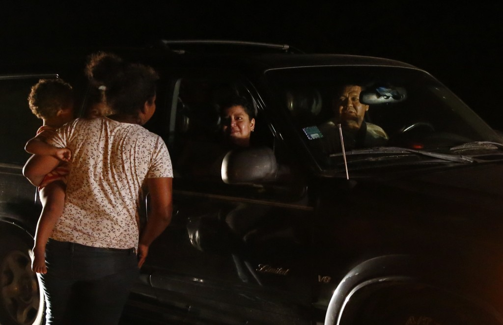 Mexicans in a car stop to talk to Honduran migrant Luz  Padilla Valverde, carrying her child, as she begs for contributions of one peso (5 cents), in