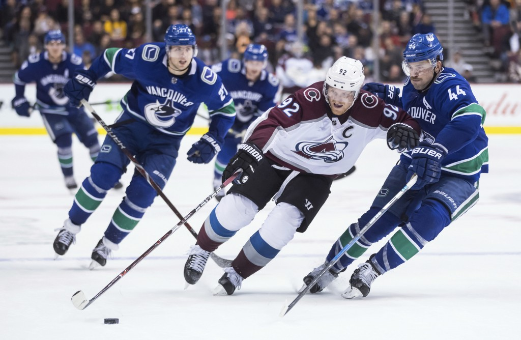 Colorado Avalanche left wing Gabriel Landeskog (92), of Sweden, tries to skate with the puck past Vancouver Canucks' Erik Gudbranson (44) as Ben Hutto...