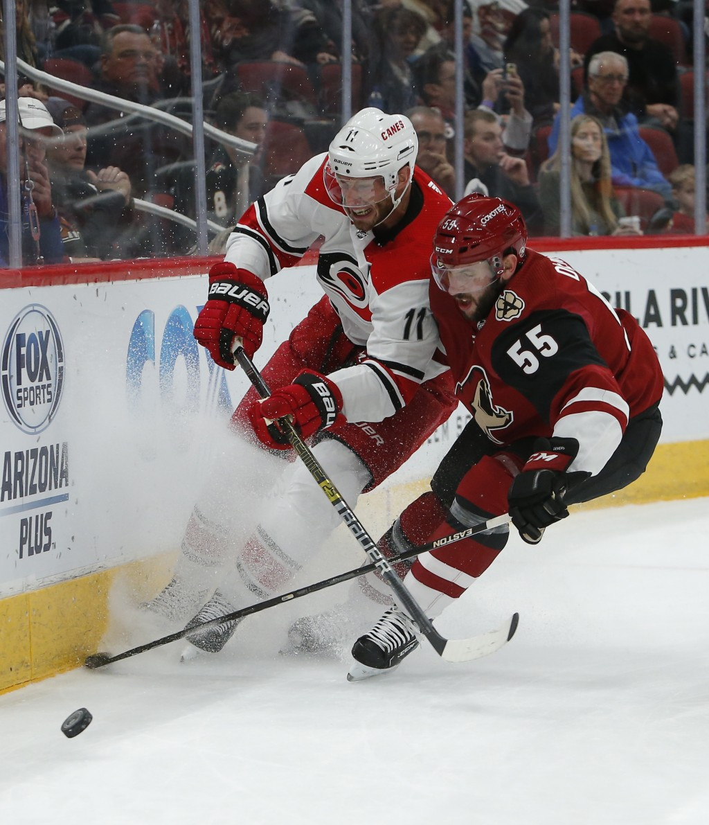 Carolina Hurricanes center Jordan Staal (11) and Arizona Coyotes defenseman Jason Demers vie for the puck during the first period of an NHL hockey gam...