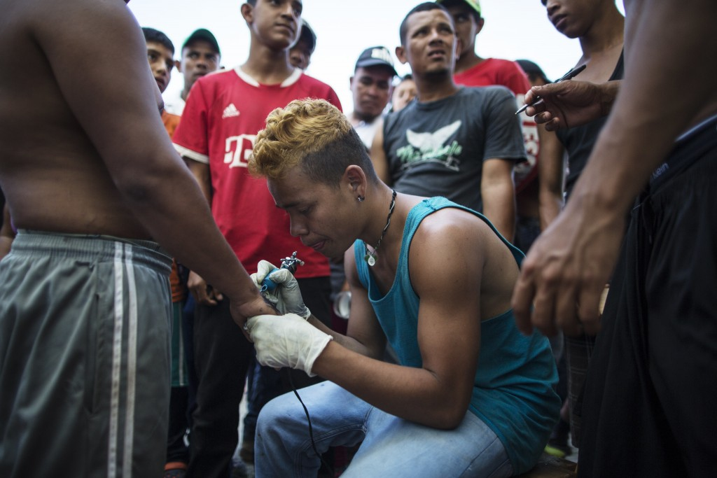 In this Oct. 31, 2018 photo, Honduran migrant Jose Manuel de Jesus Sandoval tattoos the hand of a fellow migrant, at a camp set up by a caravan of tho
