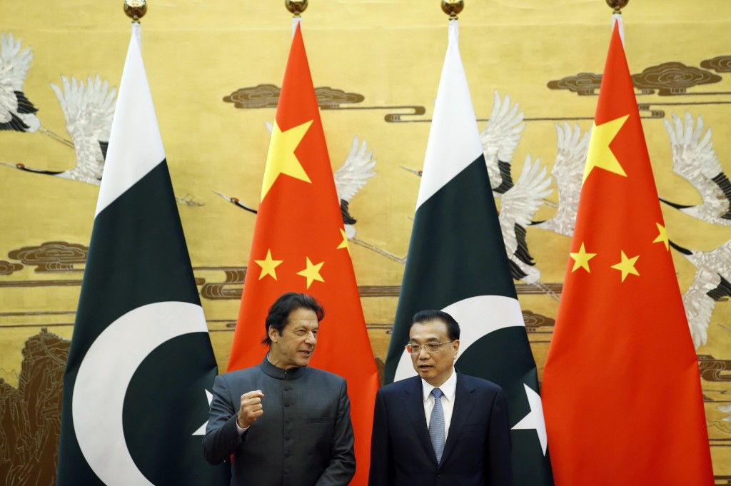 Pakistani Prime Minister Imran Khan, left, and China's Premier Li Keqiang attend a signing ceremony at the Great Hall of the People in Beijing Saturda...
