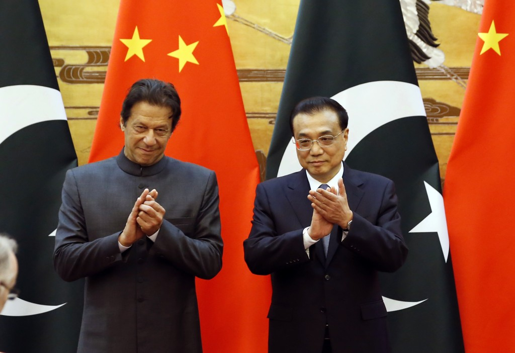 Pakistani Prime Minister Imran Khan, left, and China's Premier Li Keqiang attend a signing ceremony at the Great Hall of the People in Beijing Saturda