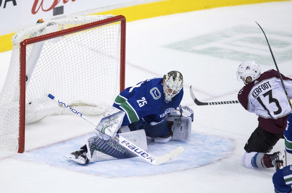 Colorado Avalanche center Alexander Kerfoot (13) scores against Vancouver Canucks goalie Jacob Markstrom, of Sweden, during the second period of an NH...