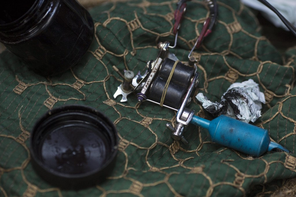 In this Oct. 31, 2018 photo, the ink and the tattoo machine used by Honduran Migrant Jose Manuel de Jesus Sandoval, sit on a cloth as he creates a tat...