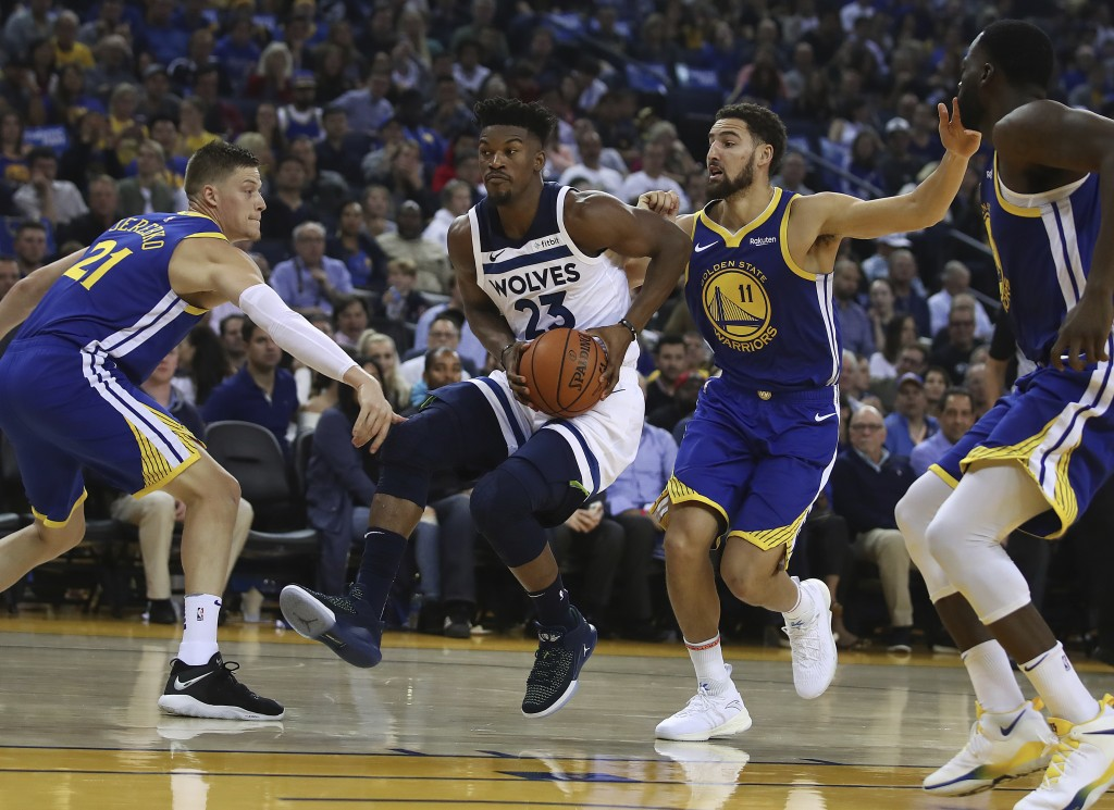 Minnesota Timberwolves' Jimmy Butler (23) drives the ball between Golden State Warriors' Jonas Jerebko, left, and Klay Thompson (11) during the first ...