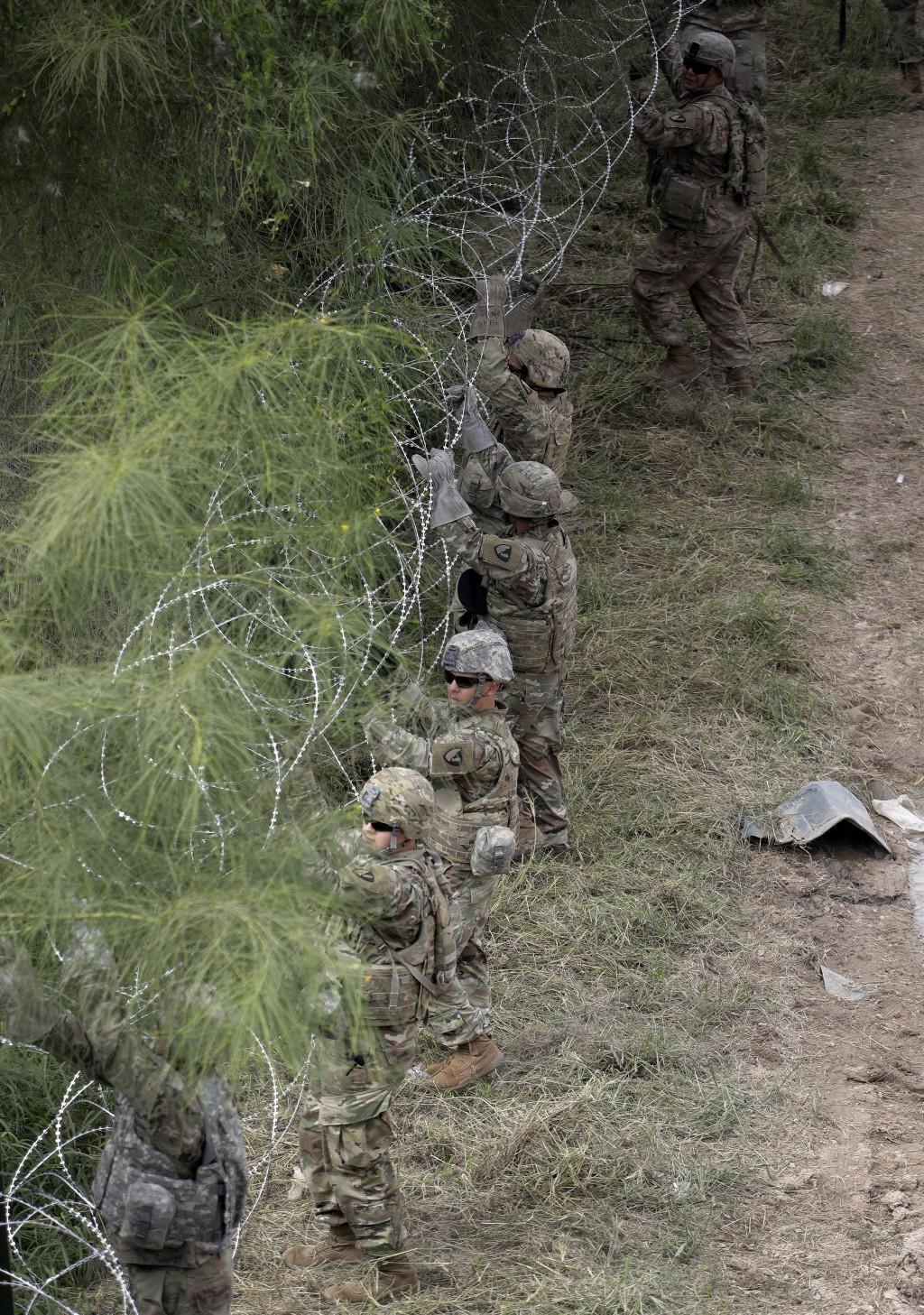 Members of the U.S. military place razor wire along the U.S.-Mexico border near the McAllen-Hidalgo International Bridge, Friday, Nov. 2, 2018, in McA