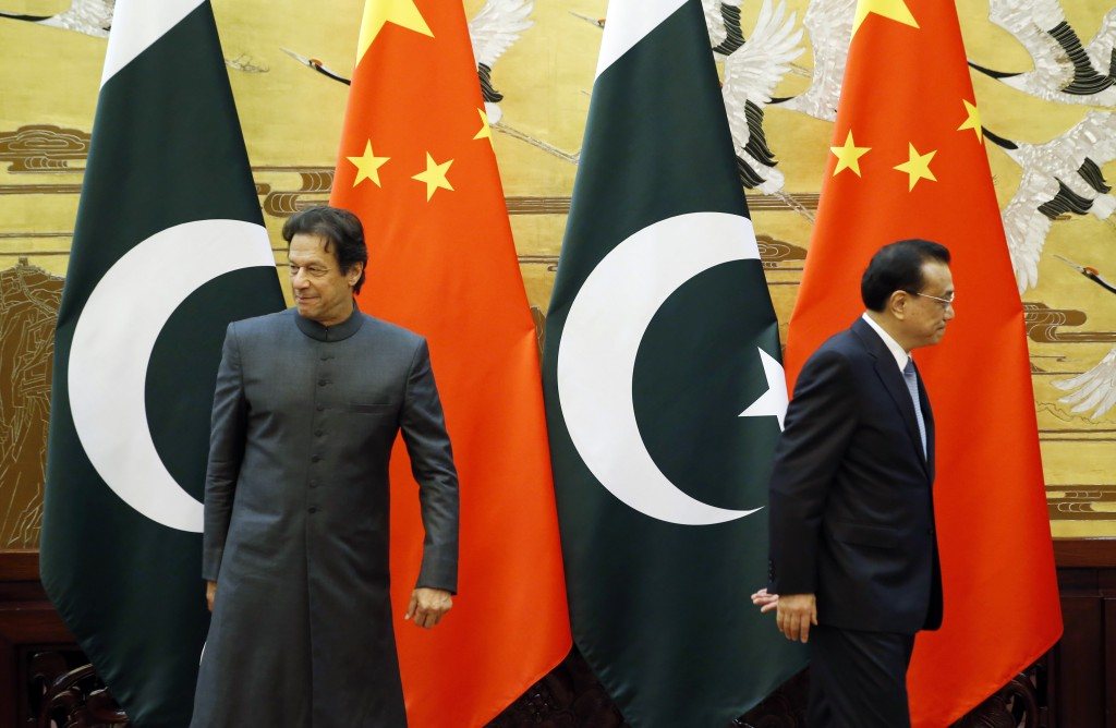 Pakistani Prime Minister Imran Khan, left, and China's Premier Li Keqiang leave after a signing ceremony at the Great Hall of the People in Beijing Sa