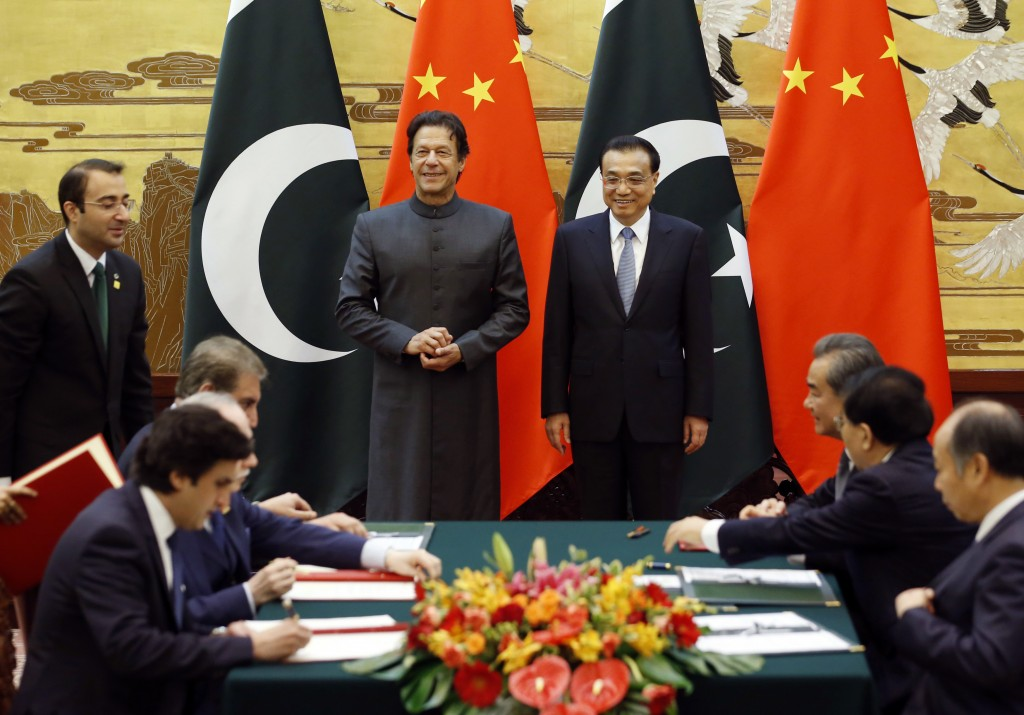 Pakistani Prime Minister Imran Khan, center left, and China's Premier Li Keqiang, center right, attend a signing ceremony at the Great Hall of the Peo...