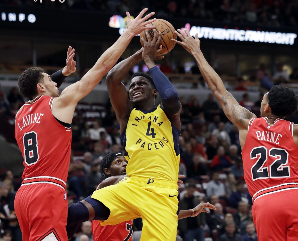 Indiana Pacers guard Victor Oladipo (4) drives to the basket against Chicago Bulls guards Zach LaVine, left, Justin Holiday, back, and Cameron Payne d...