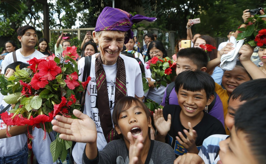 Australian Roman Catholic nun Sister Patricia Fox receives flowers from children of informal settlers as she arrives for a visit to the Redemptorist C