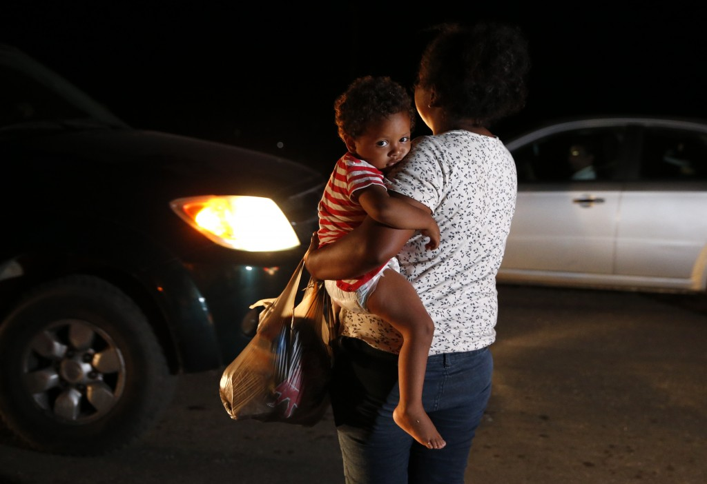 Honduran migrant Luz Padilla Valverde, carrying her child, begs for contributions of one peso (5 cents) from passing drivers, as a thousands-strong ca