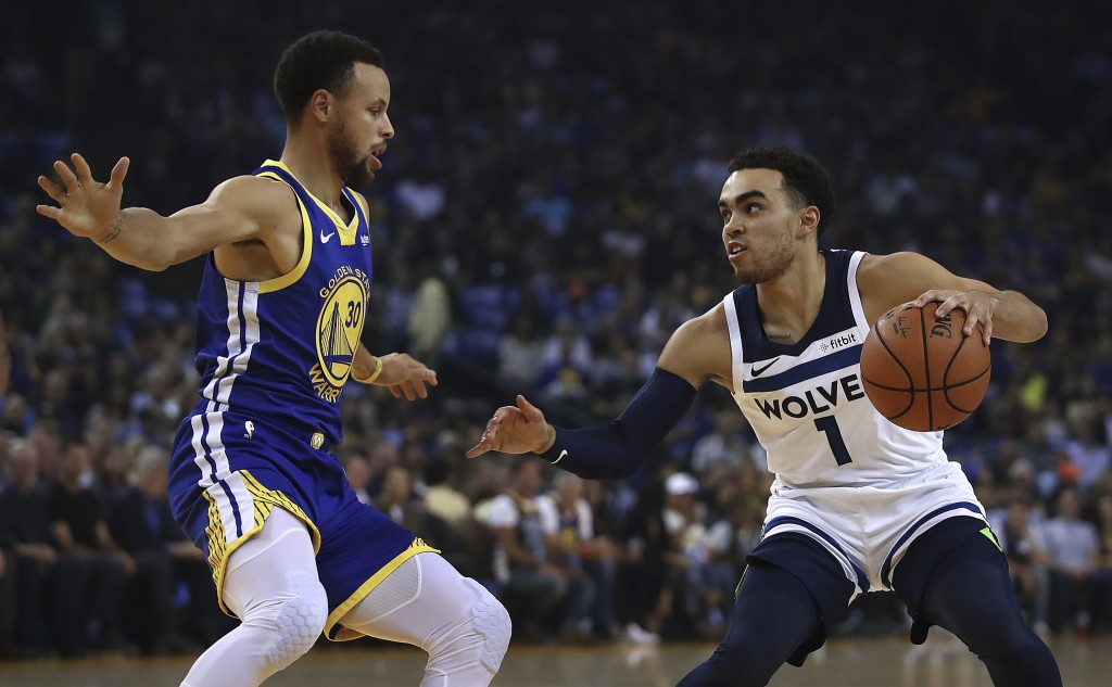 Golden State Warriors' Stephen Curry, left, defends against Minnesota Timberwolves' Tyus Jones (1) during the first half of an NBA basketball game Fri...