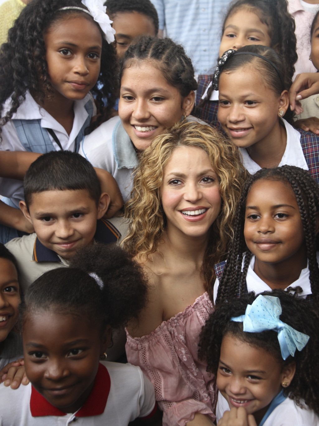 Colombian pop star Shakira posses with children after laying the cornerstone for a school her Barefoot Foundation will build in the Aranjuez neighborh...
