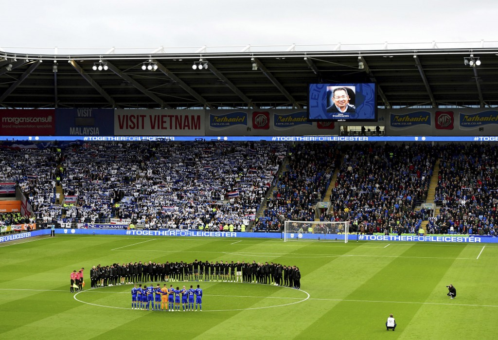 Leicester City players and staff stand with Cardiff City players and match officials during a minute's silence in memory of the victims of the Leicest...