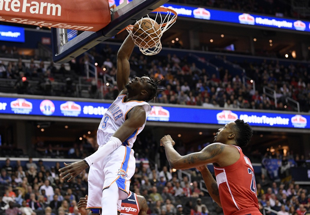 Oklahoma City Thunder forward Jerami Grant (9) dunks in front of Washington Wizards center Dwight Howard, right, during the first half of an NBA baske...